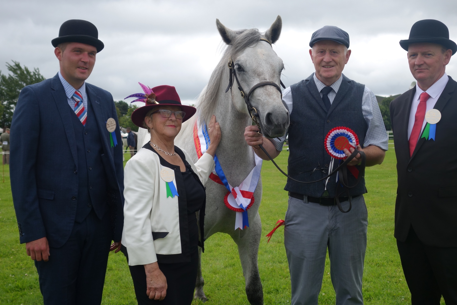 Judge Peter O'Malley, right, with fellow judges & Connemara Pony Class Winner James Naan, second right, at the Omagh Show