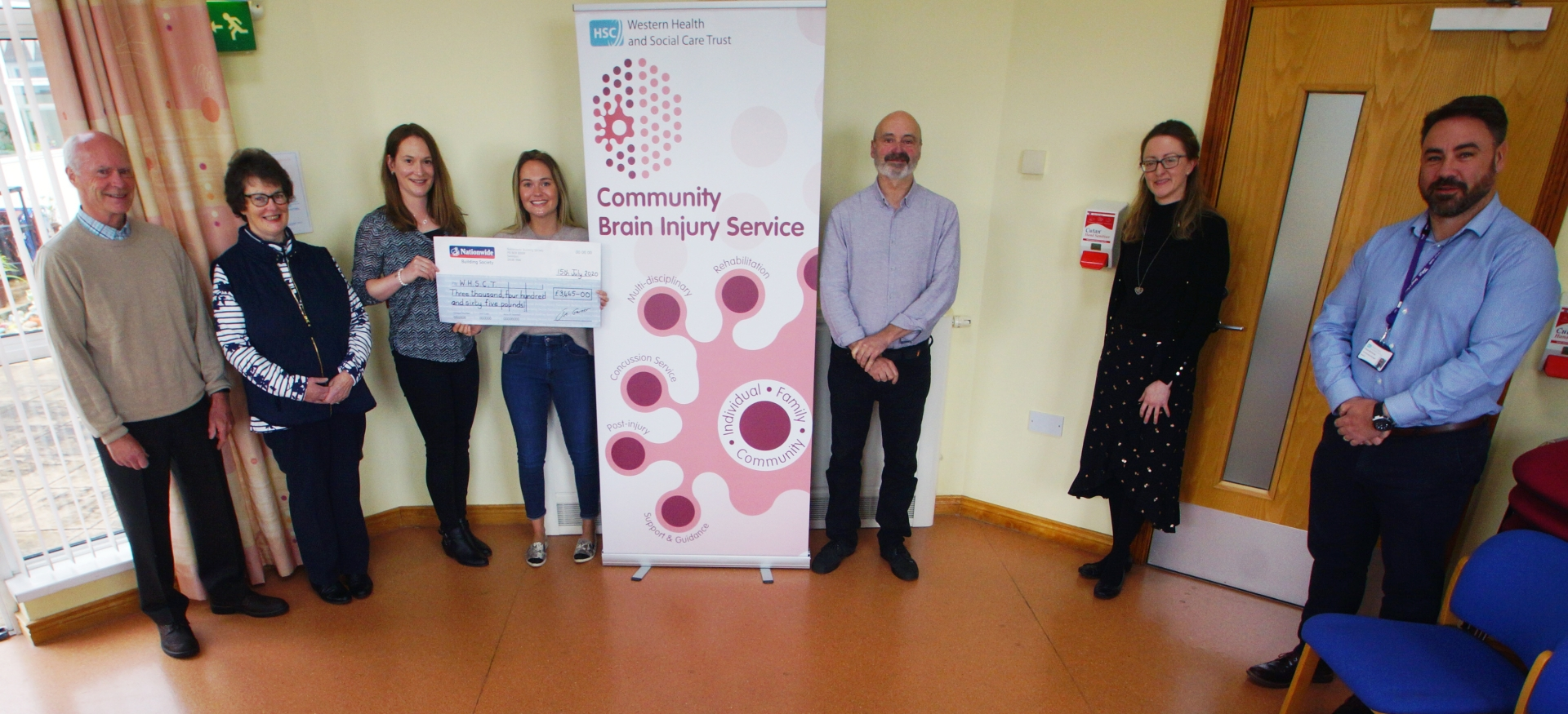 Pictured yesterday at the handing over of the cheque are, from left, Katie's parents, John and Wendy, Lizzie, Katie, Dr Paul Johnston, clinical psychologist, Carmel Greene, occupational therapist, and Dr Shane McCarney, consultant clinical lead at the Community Brain Injury Team in Derry